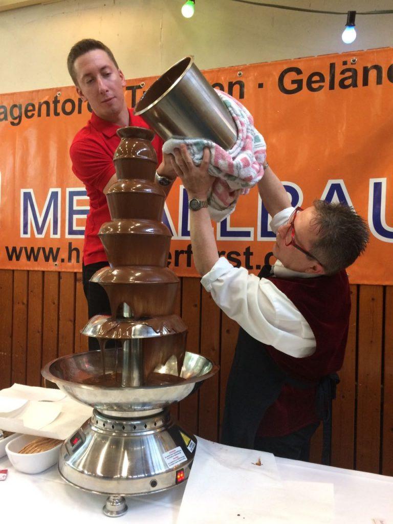 Clemens Backs mit Kollegen befüllen den Schokobrunnen