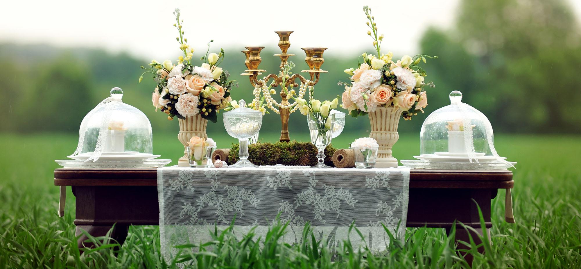 Tisch welcher mit Tischdecke,Blumen, Kerzenständer dekoriert ist