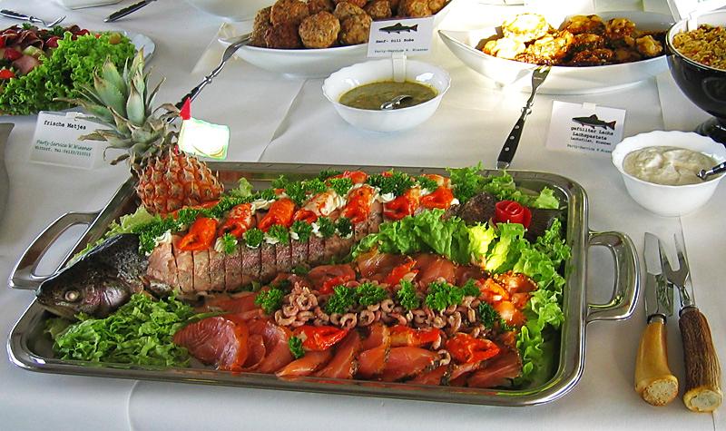 Fischplatte steht mit Besteck und anderen Gerichten auf einem Tisch